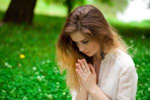 Das Bild zeigt ein junges Mädchen, das in der Wiese sitzt und betet.